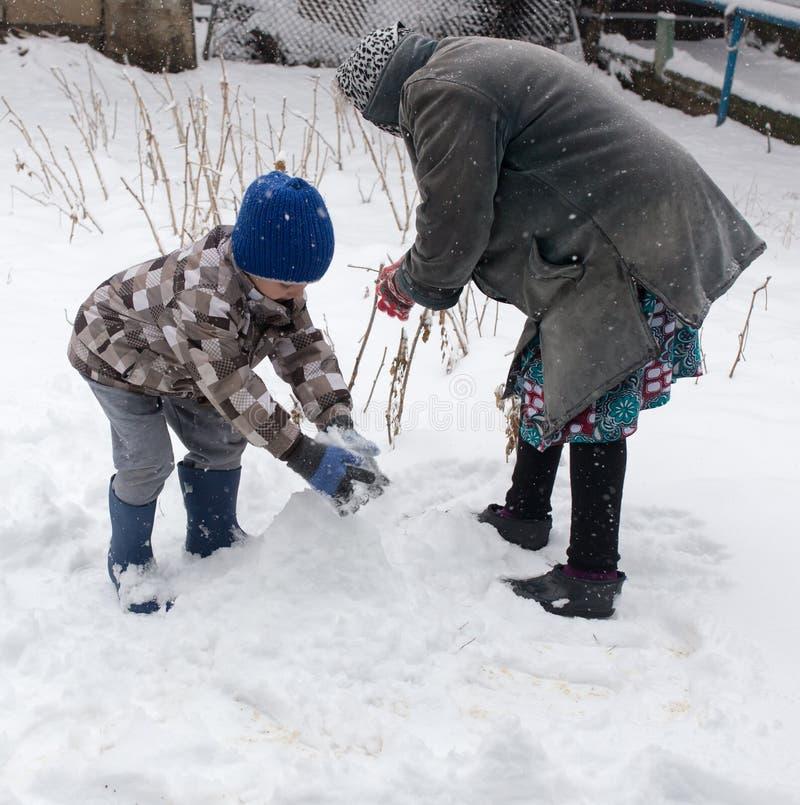 Chłopiec z jego babcią bawić się w śniegu zdjęcia royalty free