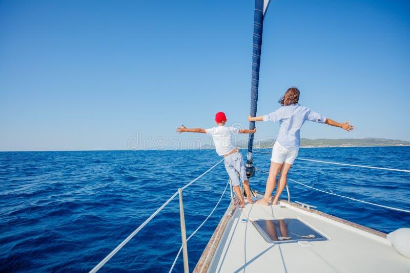 Chłopiec z jego matką na pokładzie żeglowanie jachtu na lato rejsie fotografia royalty free