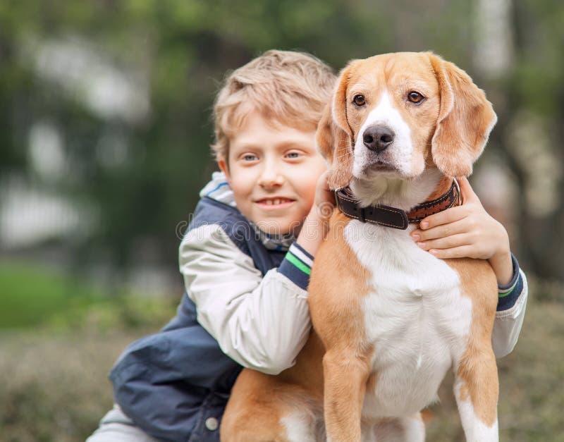 Chłopiec z jego psem jest w wiosna parku zdjęcie royalty free
