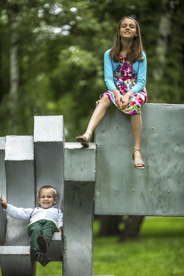 Chłopiec z jego starą siostrą na boisku w parku Zabawa obrazy stock