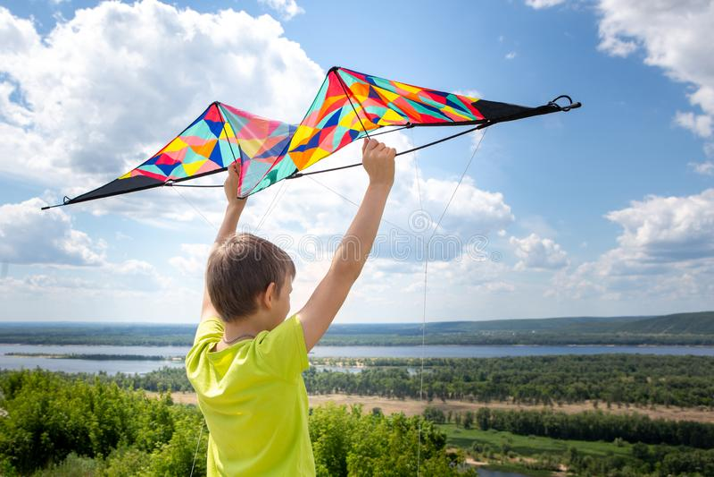 Chłopiec z kolorową kanią w jego rękach przeciw niebieskiemu niebu z chmurami Dziecko w żółtej koszulce i skrótach pi?kne obraz stock