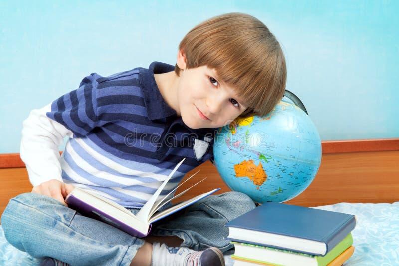 Chłopiec z książkami i kulą ziemską obraz stock
