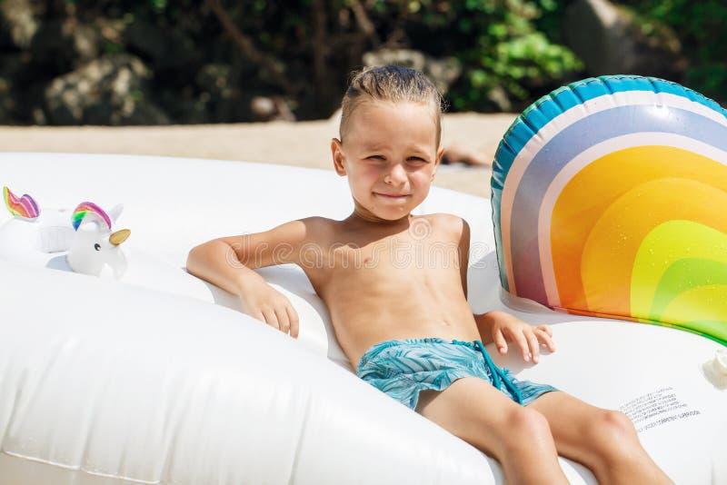 Chłopiec z nadmuchiwaną jednorożec na plaży zdjęcia royalty free