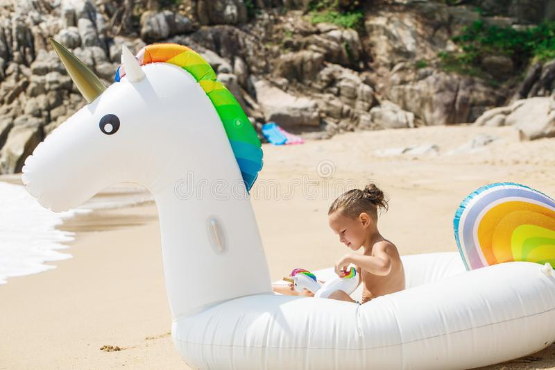 Chłopiec z nadmuchiwaną jednorożec na plaży obraz stock