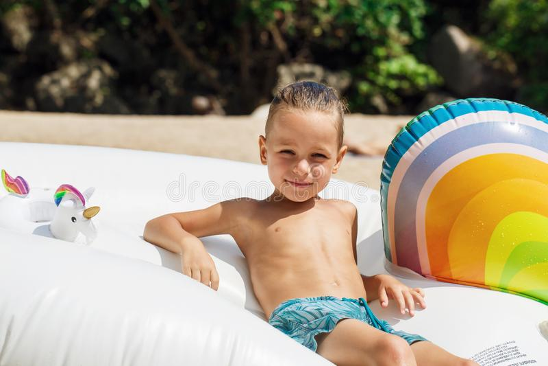 Chłopiec z nadmuchiwaną jednorożec na plaży fotografia royalty free