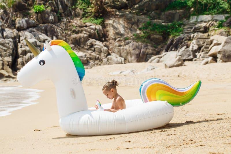 Chłopiec z nadmuchiwaną jednorożec na plaży fotografia stock