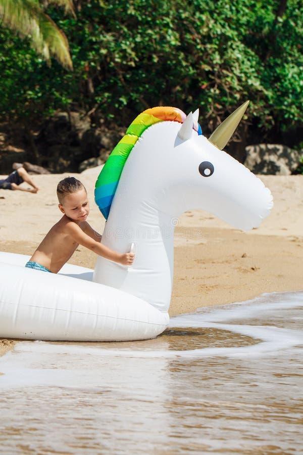 Chłopiec z nadmuchiwaną jednorożec na plaży zdjęcie stock