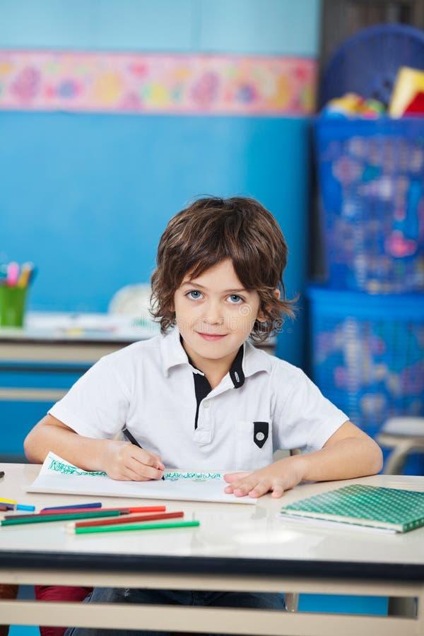 Chłopiec Z nakreślenia pióra rysunkiem W sala lekcyjnej fotografia royalty free