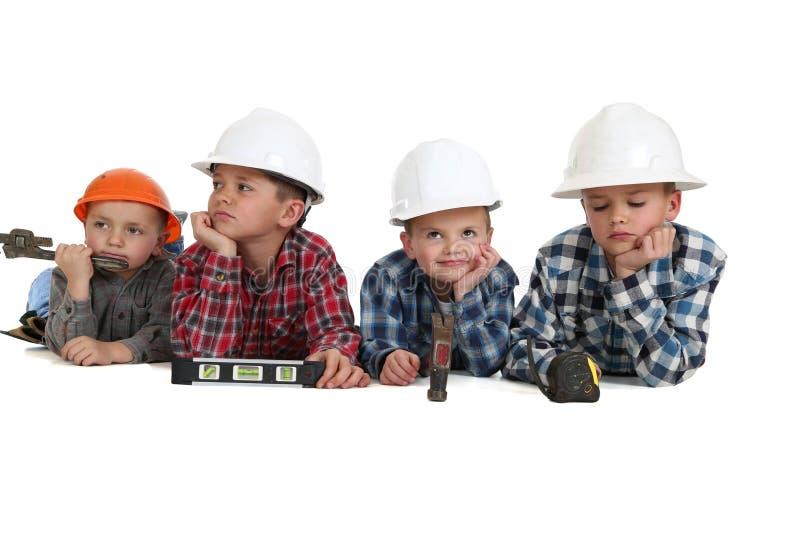 Chłopiec z narzędziami i hardhats na ich żołądkach fotografia stock