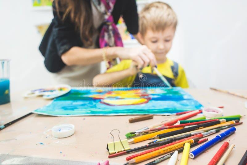 Chłopiec z nauczycielem w grupie preschool uczeń siedział rysunek obrazek Malujący na maelbert, paleta i obraz stock