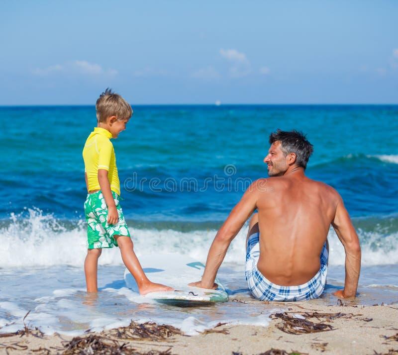 Chłopiec z ojca surfingiem obrazy royalty free