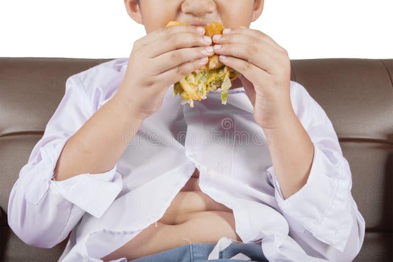 Chłopiec z potbelly cieszy się cheeseburger zdjęcie stock
