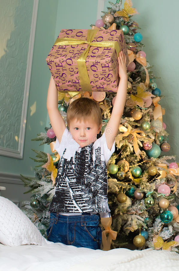 Chłopiec z prezenta pudełkiem w rękach zbliża drzewa obrazy stock