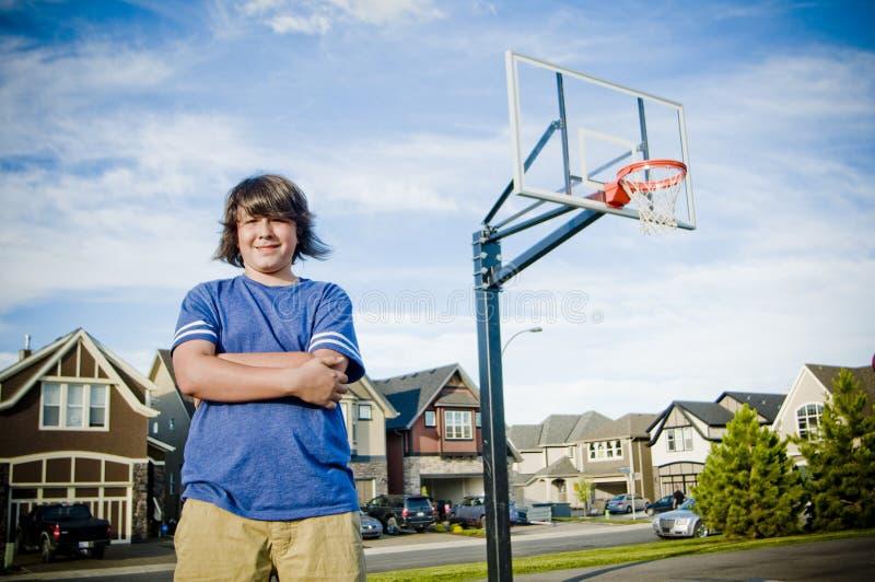Chłopiec z rękami krzyżować z koszykówki sieci ono uśmiecha się obraz royalty free