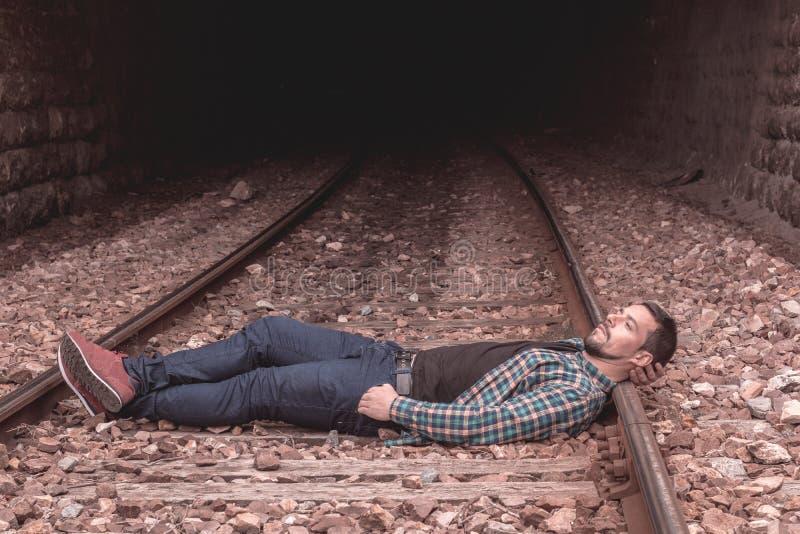 Chłopiec z rozważną twarzą poważną postawą i Obrazek na pociągów śladach, obsługuje przypadkową suknię obrazy royalty free