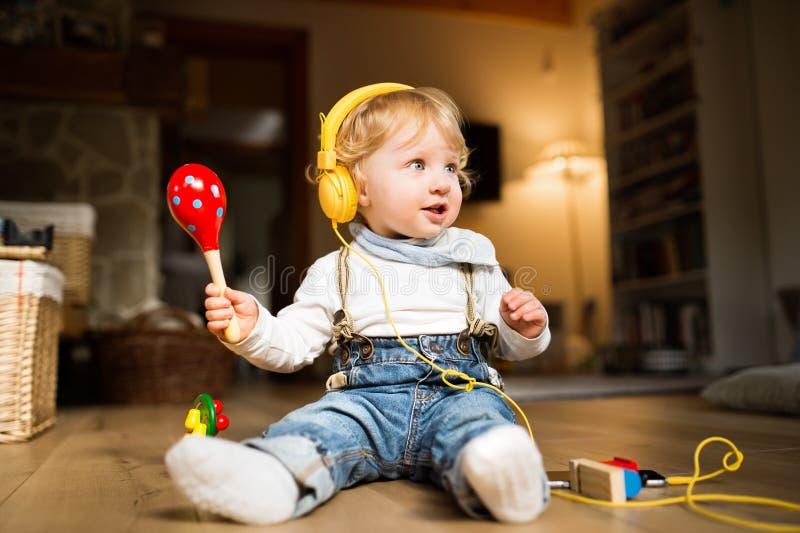 Chłopiec z słuchawkami, słuchającą muzyką wewnątrz i kursowanie musicalem, fotografia royalty free