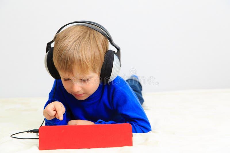 Chłopiec z słuchawki używać dotyka ochraniacza obraz stock
