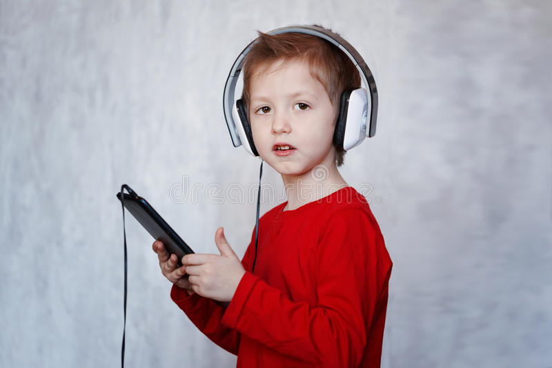 Chłopiec z słuchawki używać dotyka ochraniacza, słucha muzyka z obraz royalty free