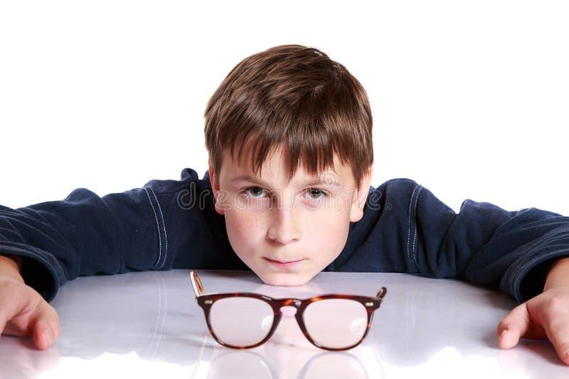 Chłopiec z szkłami i niskim wzrokiem obraz stock