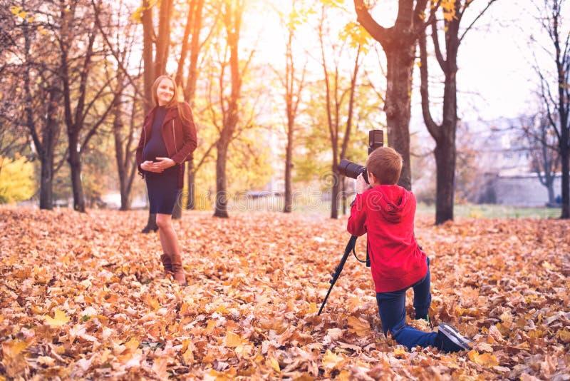 Chłopiec z wielką refleksową kamerą na tripod Fotografuje kobiety w ciąży Rodzinnej fotografii sesja zdjęcie stock