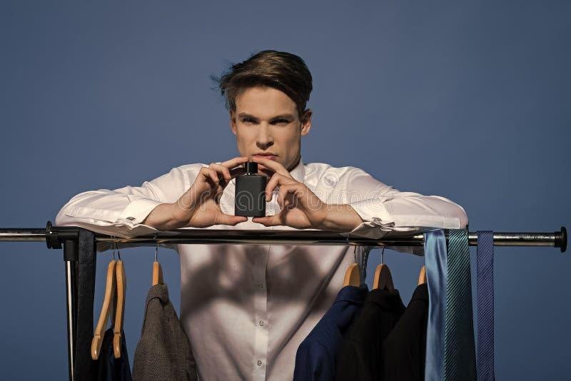 Chłopiec Zasilająca Zagadnienie twarzy chłopiec Mężczyzna chwyta pachnidło w garderobie na błękitnym tle obrazy royalty free