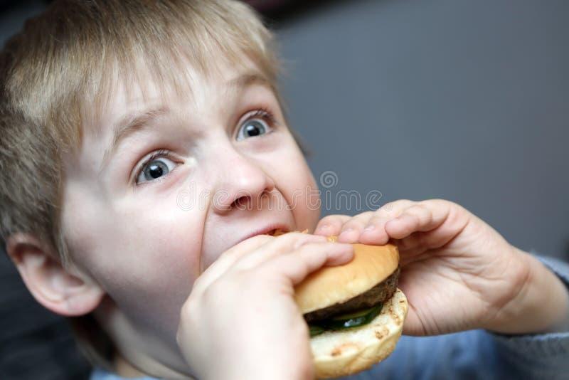 Chłopiec zjadliwy hamburger obrazy stock