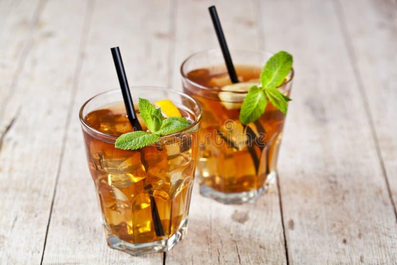 Ch? gelado tradicional com lim?o, folhas de hortel? e cubos de gelo em dois vidros na tabela de madeira r?stica imagens de stock