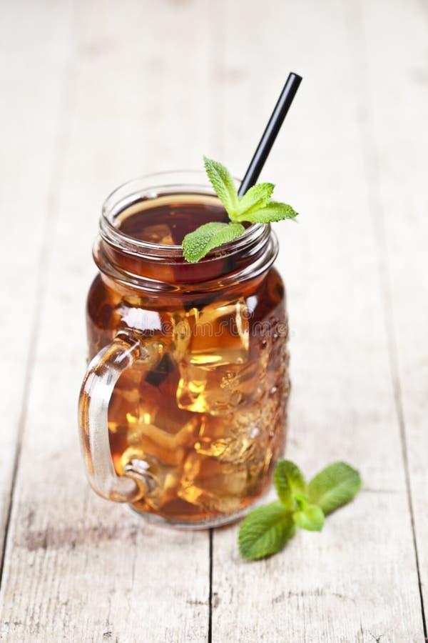 Ch? gelado tradicional com lim?o, folhas de hortel? e cubos de gelo no frasco de vidro na tabela de madeira r?stica imagem de stock royalty free