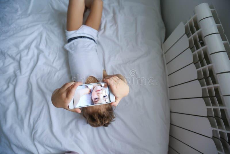 Ch?opiec bawi? si? na elektronicznej gad?et pastylce w jego sypialni Og?lnospo?eczny problem komunikacja dzieci w wsp??czesnym ?w zdjęcie stock