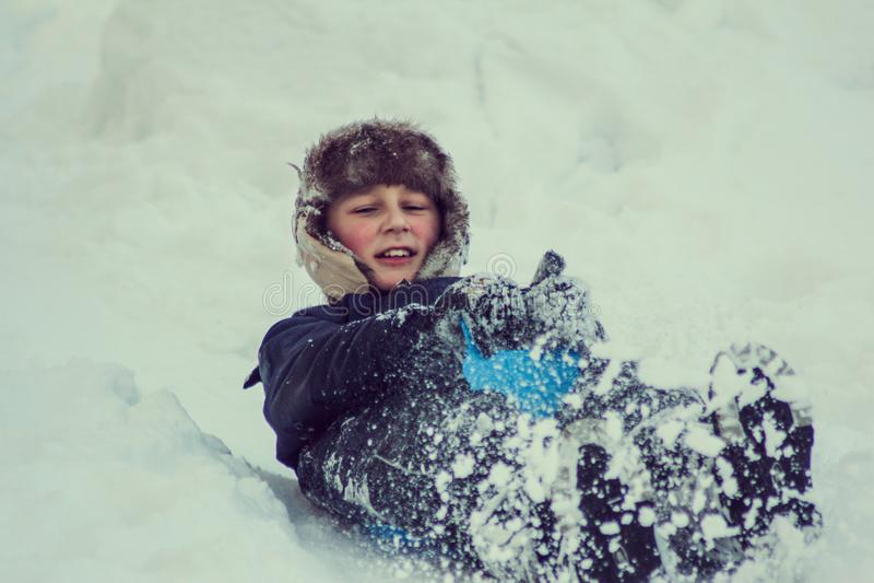 Ch?opiec cieszy si? sanie przeja?d?k? Dziecka sledding Berbecia dzieciak jedzie saneczki Dziecko sztuka outdoors w ?niegu ?artuje zdjęcie royalty free