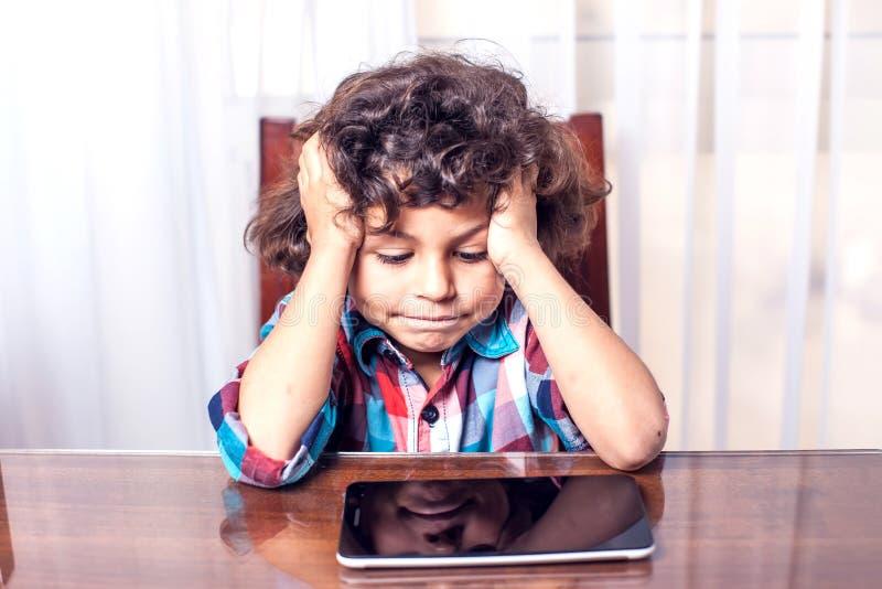 Ch?opiec patrzeje dotyka ochraniacza w domu Dzieci, technologii pojęcie fotografia royalty free