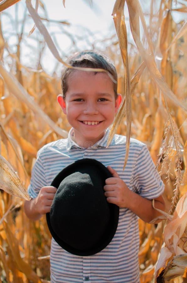 ch?opiec szcz??liwy u?miech Śliczna potomstw 10 roczniaka chłopiec z czarnym kapeluszem w jego ręki Dziecko w kukurydzanym polu - fotografia stock