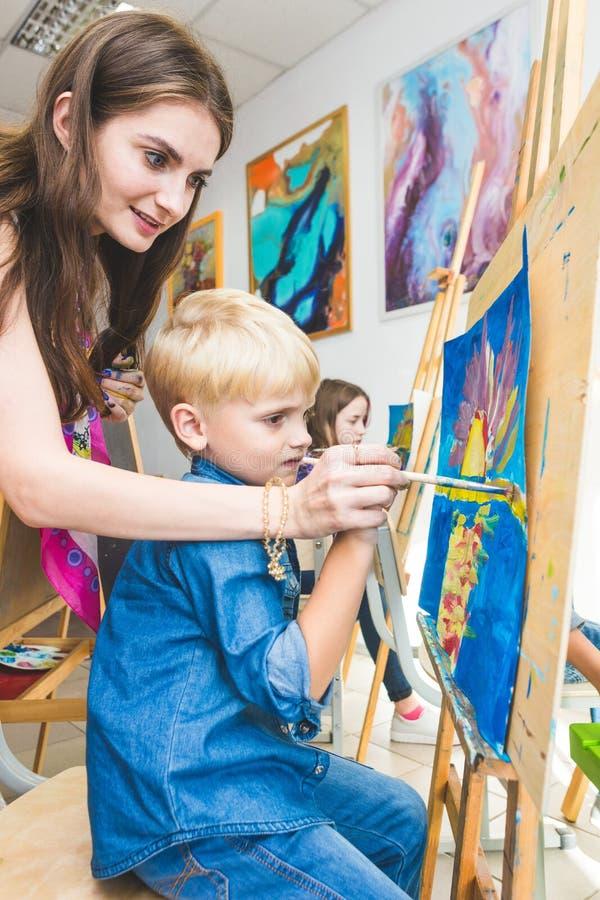 Ch?opiec z nauczycielem w grupie preschool ucze? siedzia? rysunek obrazek Maluj?cy na maelbert, paleta i obraz royalty free