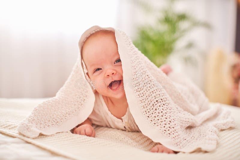 Ch?ri sous l'essuie-main un petit enfant gai regarde de dessous la couverture et les sourires drôles mensonge sur son estomac sur image libre de droits