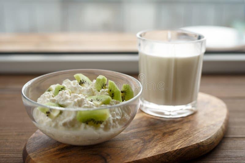Chałupa ser z kiwi i szkłem mleko na drewnianej desce, pojęcia zdrowy jedzenie zdjęcia royalty free
