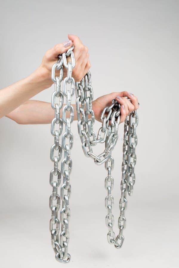 Chaîne épaisse en métal chez les mains des femmes sur le fond blanc d'isolement images stock
