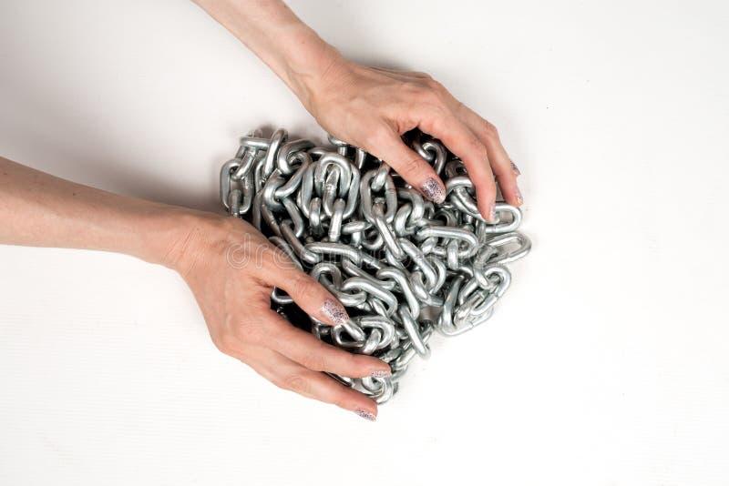 Chaîne épaisse en métal chez les mains des femmes sur le fond blanc d'isolement photo libre de droits