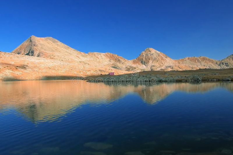Chaîne de montagne avec sa réflexion dans le lac glaciaire avoisinant photos stock