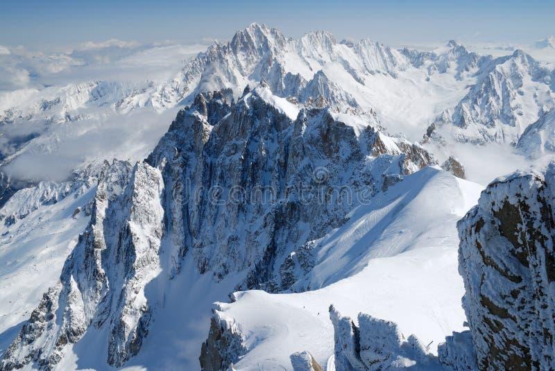 Chaîne de montagne parmi la neige et les nuages, les Alpes photo libre de droits