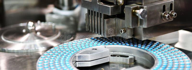 Chaîne de production bleue de pilule de médecine de capsule photographie stock libre de droits