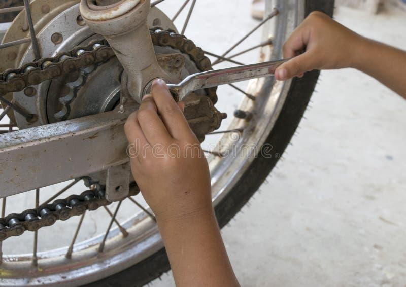 Chaîne de réparation d'enfant de moto photo stock