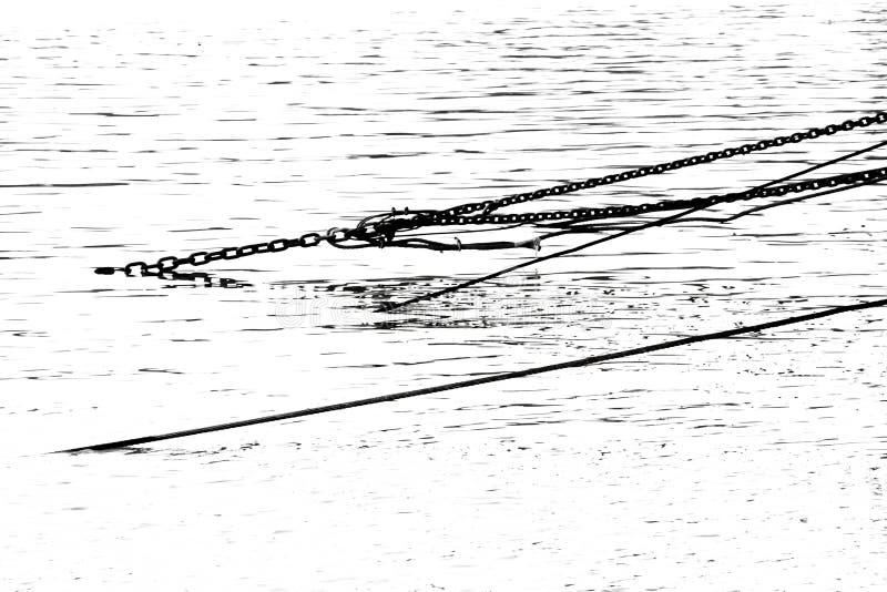 Chaîne en acier de câble et de fer dans l'eau en noir et blanc photos stock