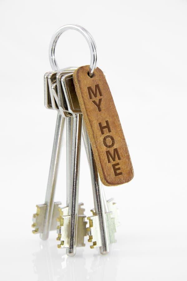 Chaîne principale en cuir avec des clés sur le fond blanc d'isolement Ma maison image libre de droits