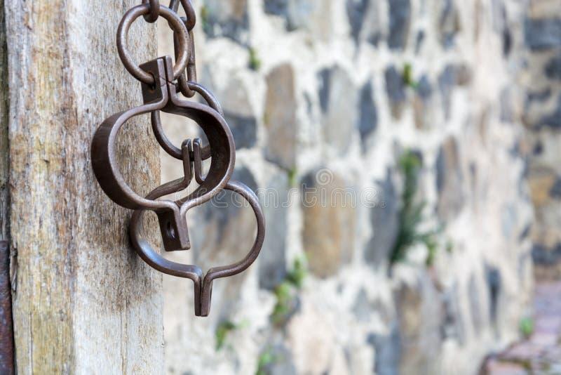 Chaînes médiévales de prison pour des prisonniers devant le mur en pierre images stock