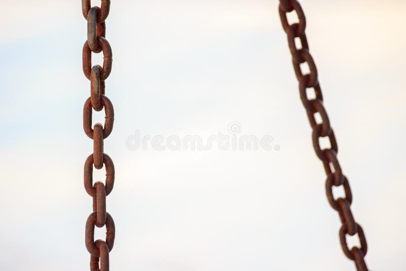 Chaînes rouillées sur un fond clair, partie au foyer punition, attache image stock