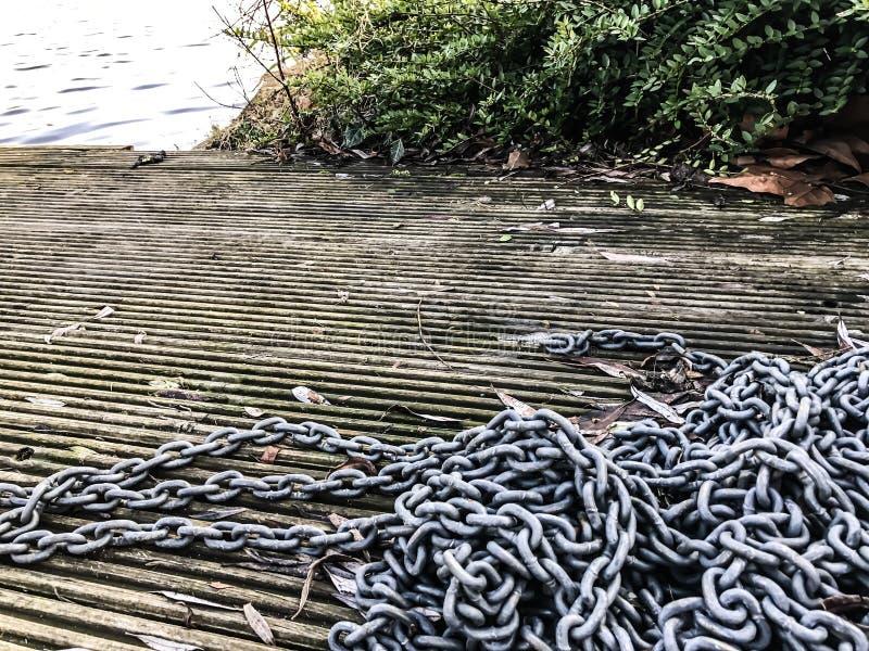 Chaînes sur le dock en bois de flottement photo stock