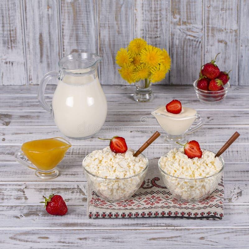 Chałupa ser, kwaśna śmietanka, mleko, czerwona truskawka i miód na stole, fotografia royalty free