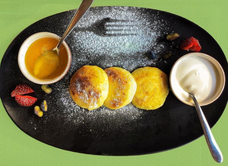 Chałupa sera bliny lub Rosyjski sirniki z miodem c i podśmietaniem zdjęcia stock