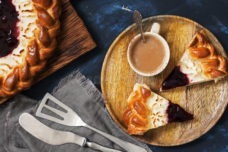 Chałupy cheesecake z jagodowym dżemem i kawą na zmroku - błękitny tło Odgórny widok, płaski lying on the beach fotografia stock