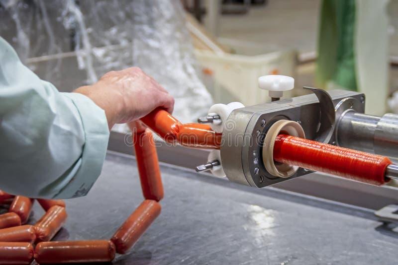 Cha?ne de production de saucisse Les ouvriers de saucisse produit les saucisses bouillies Chaîne de production moderne de sauciss images libres de droits